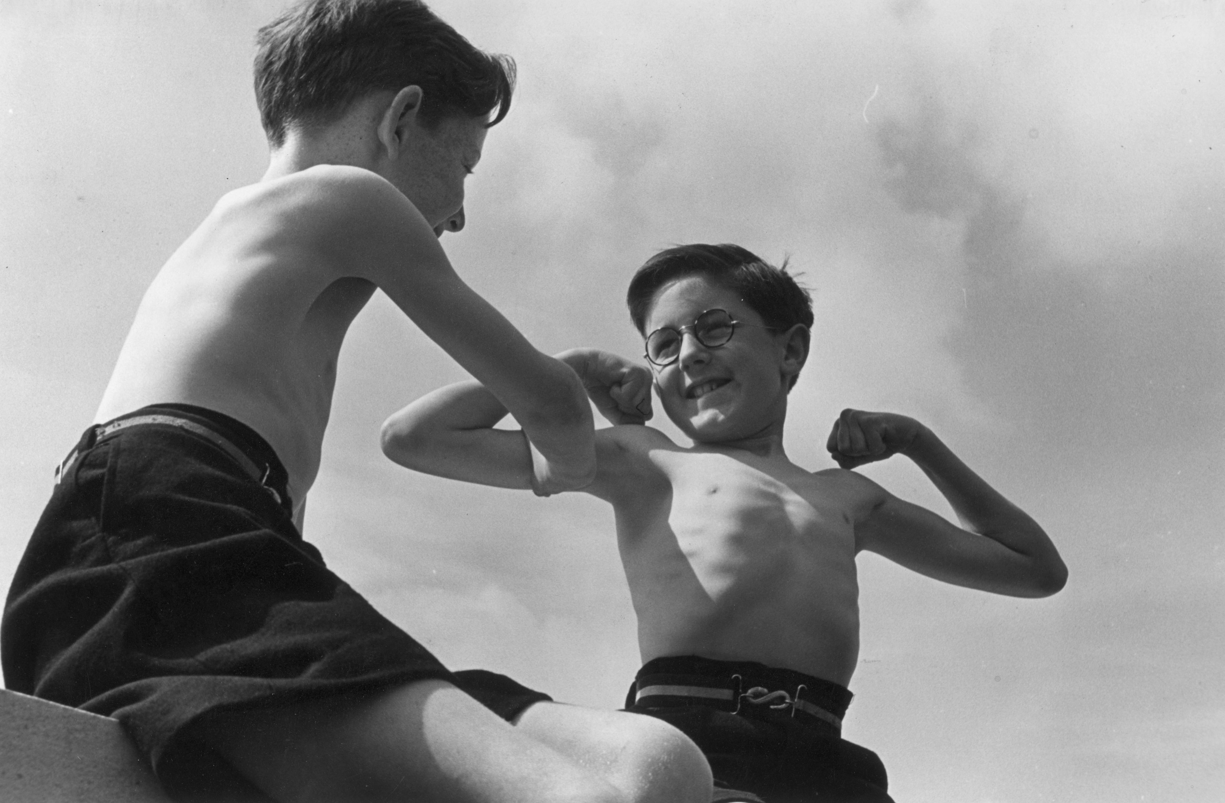 Two boys comparing their muscles