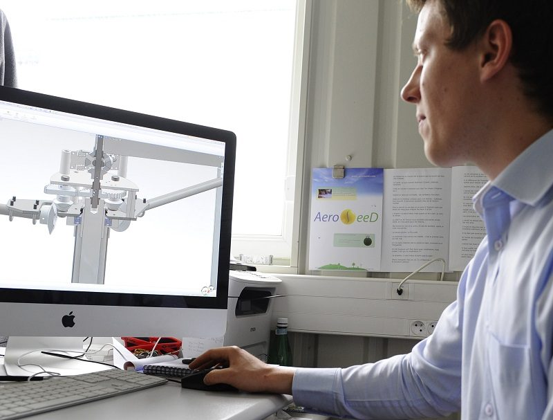 A mechanical engineer works on a model of a wind turbine