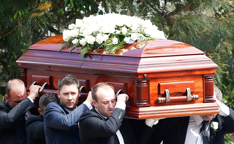 Pallbearers carry the coffin of an Australian cricket legend during a funeral