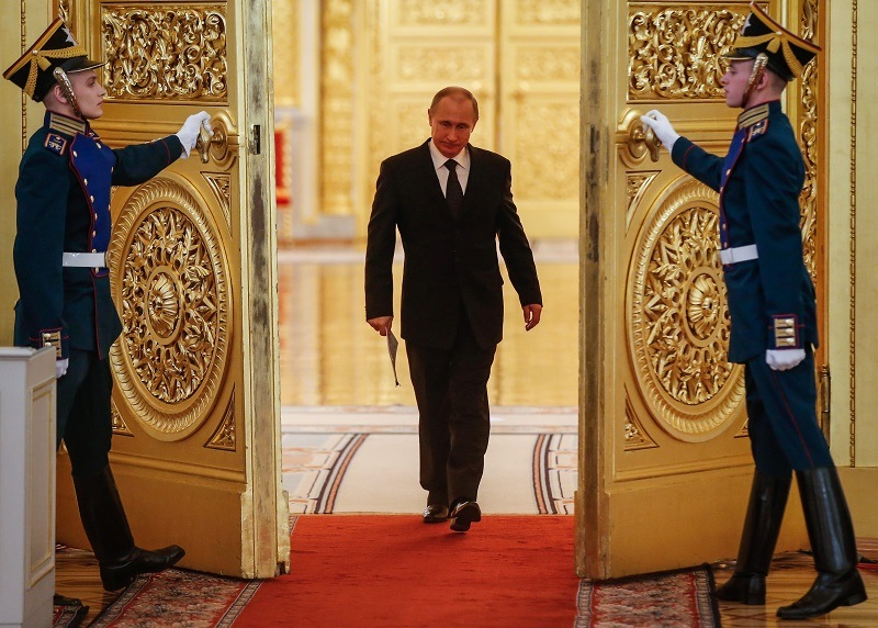 Vladimir Putin walks through an ornate gold door with guards on either side of him