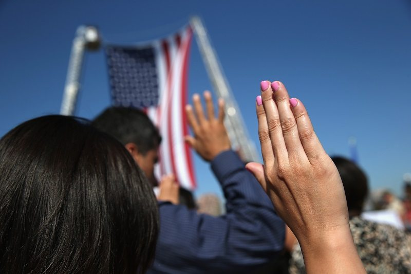 Immigrants take part in a naturalization ceremony