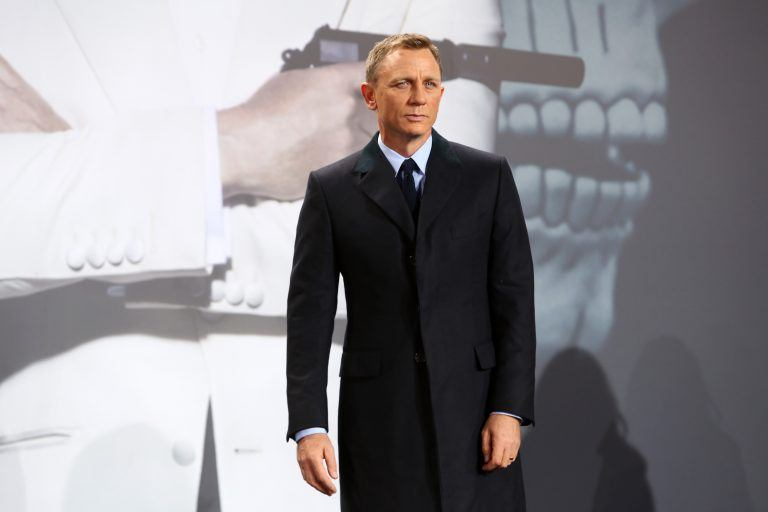 Daniel Craig poses in a black coat