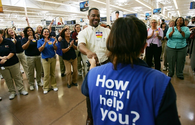 A Walmart associate receives a promotion in front of cheering coworkers, advancing her career path