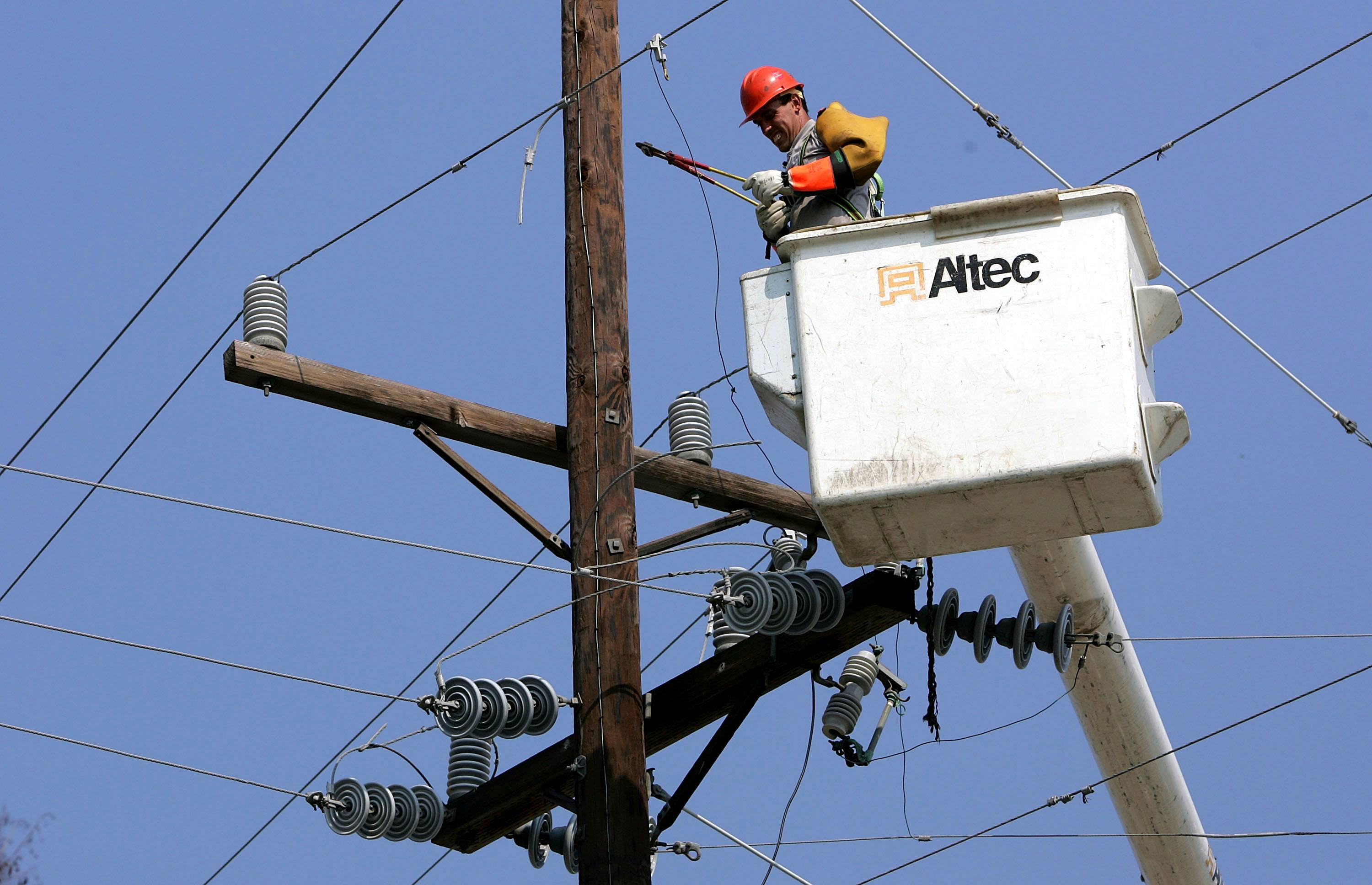 A utility worker repairs a power line