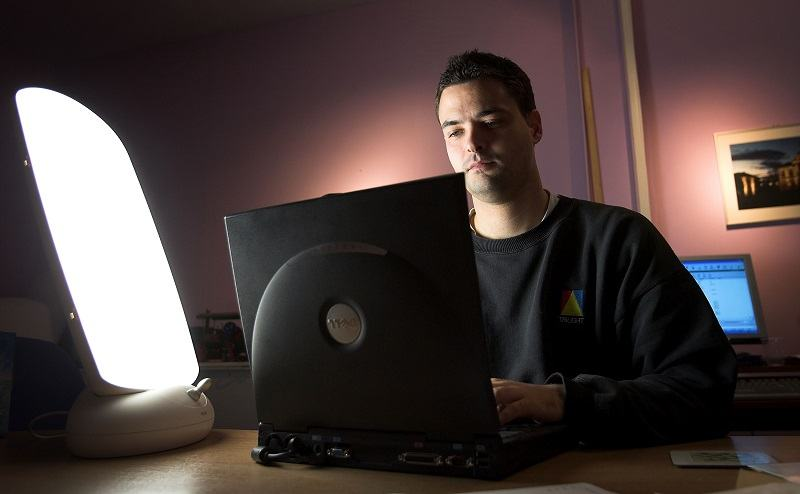 A man suffering from seasonal depression, a common mental health issue, sits in front of a natural light box in his office