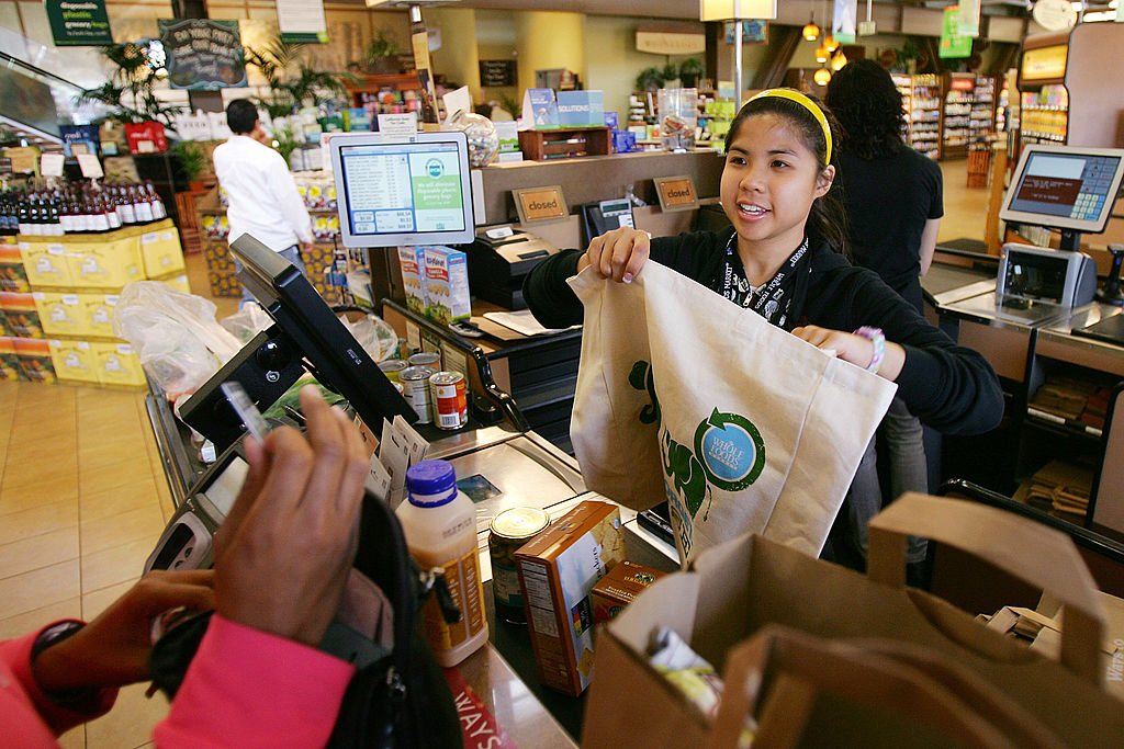 A cashier hands out free reusable grocery bags at a Whole Foods
