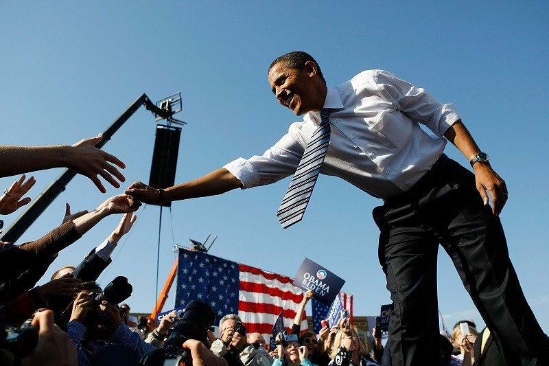 Barack Obama shakes hands with people during a campaign rally