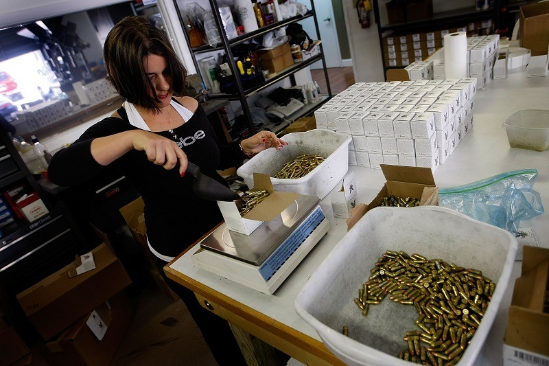 A worker weighs a box of 5.56mm cartridges as she packages them for shipping