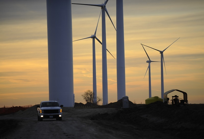 Wind turbines stand at sunset in rural Kansas