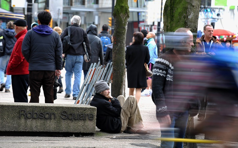 A homeless man sits on the street in downtown Vancouver, emblematic of the city's affordable housing crisis