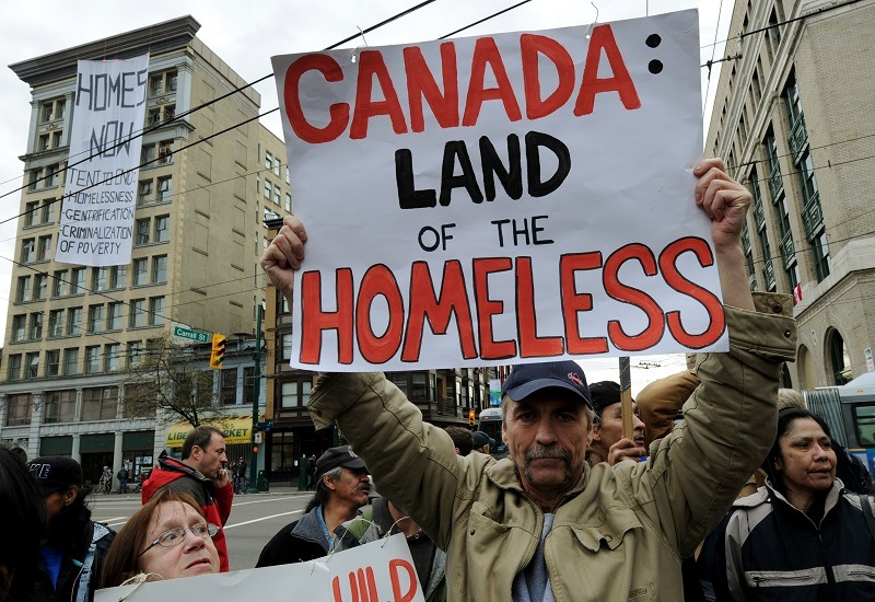 A man protests against homelessness near the Olympic Tent Village during the 2010 Winter Olympics