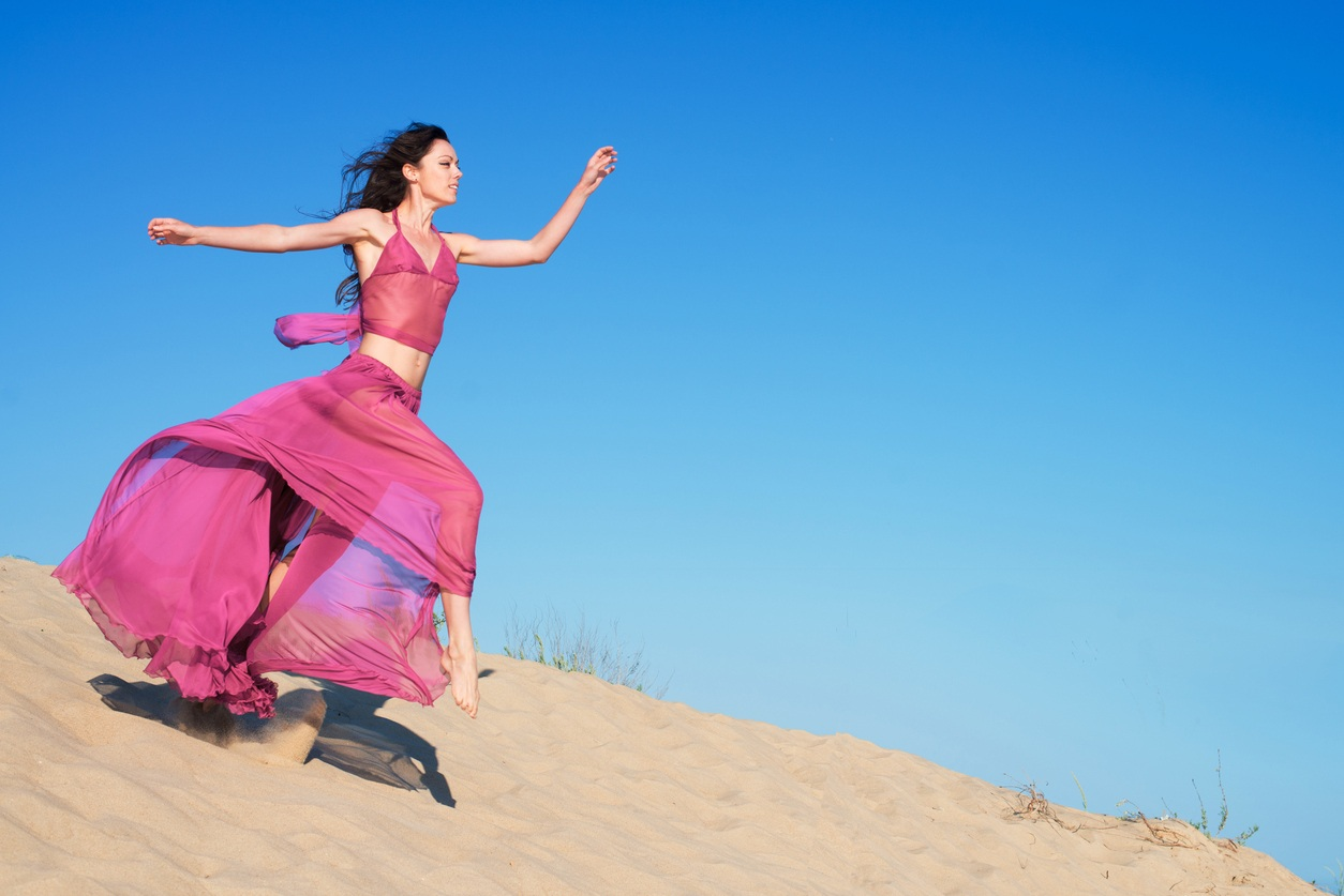 beautiful girl in an airy dress running on sand dunes