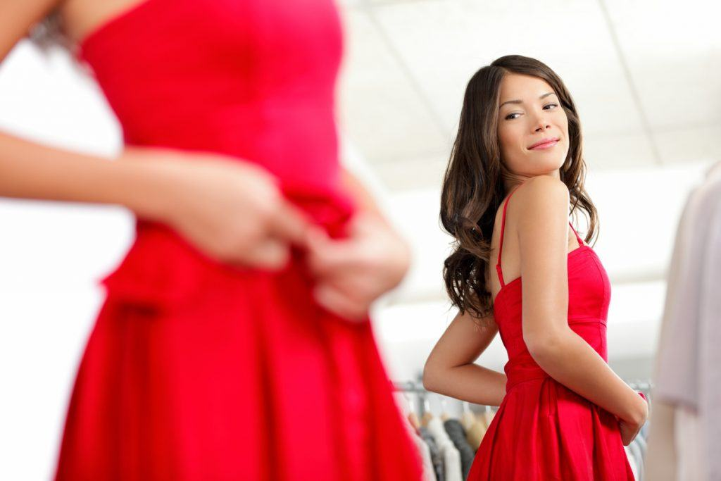 girl trying dress in looking in mirror cheerful and happy