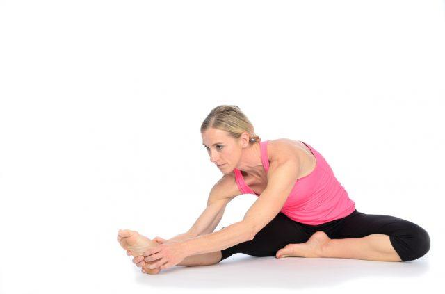 woman in pink and black outfit doing leg stretch