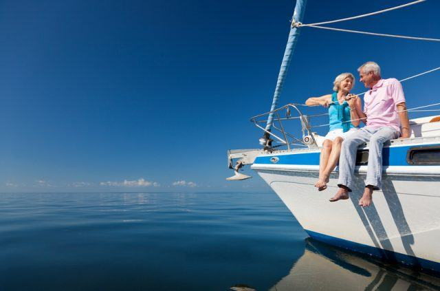 A happy senior couple sitting on the front of a sail