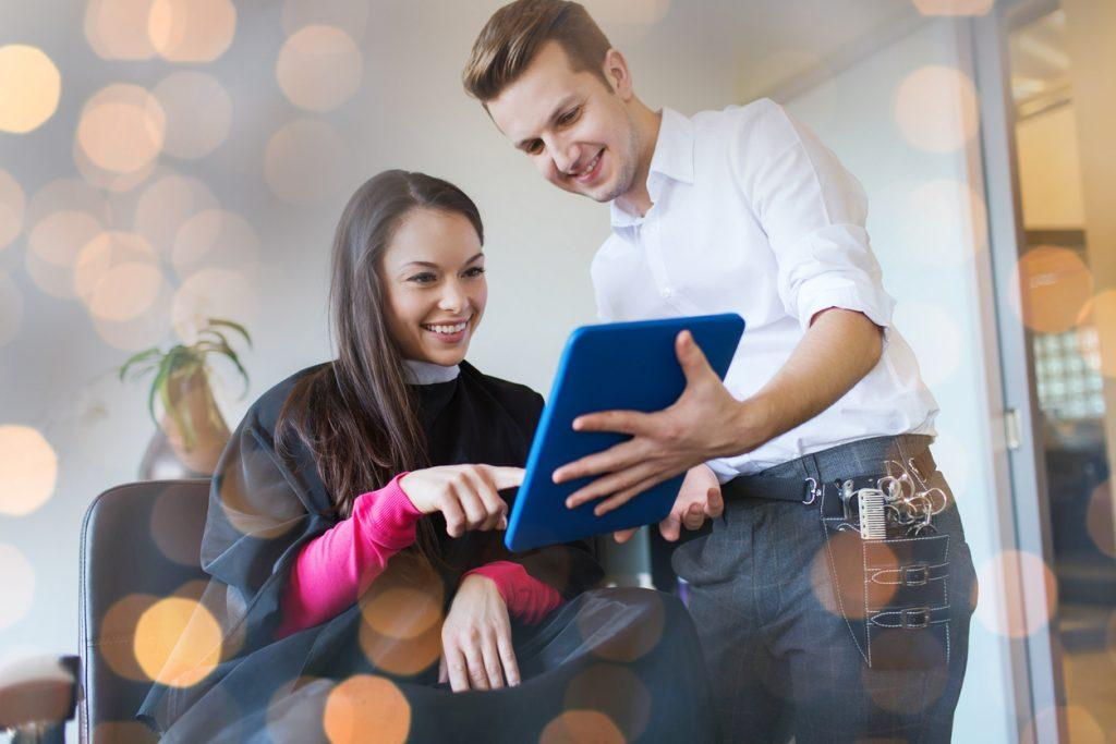 happy young woman and stylist with tablet pc