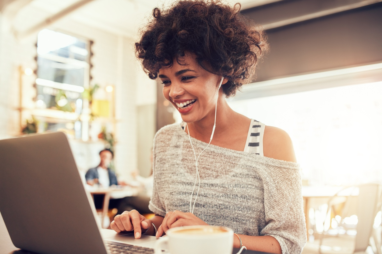 Young african american woman sitting in a coffee shop and working on laptop