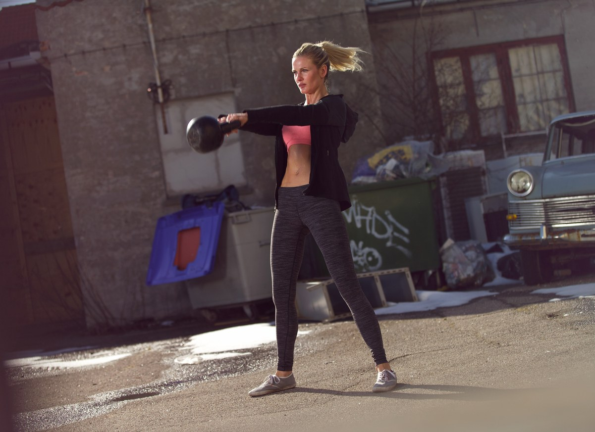 woman swinging the kettlebell during gym training