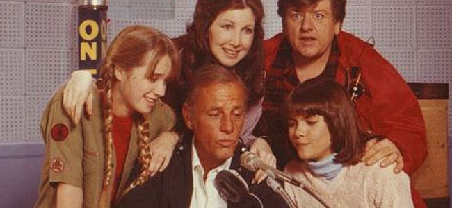 The cast of Hello Larry gathers around a microphone