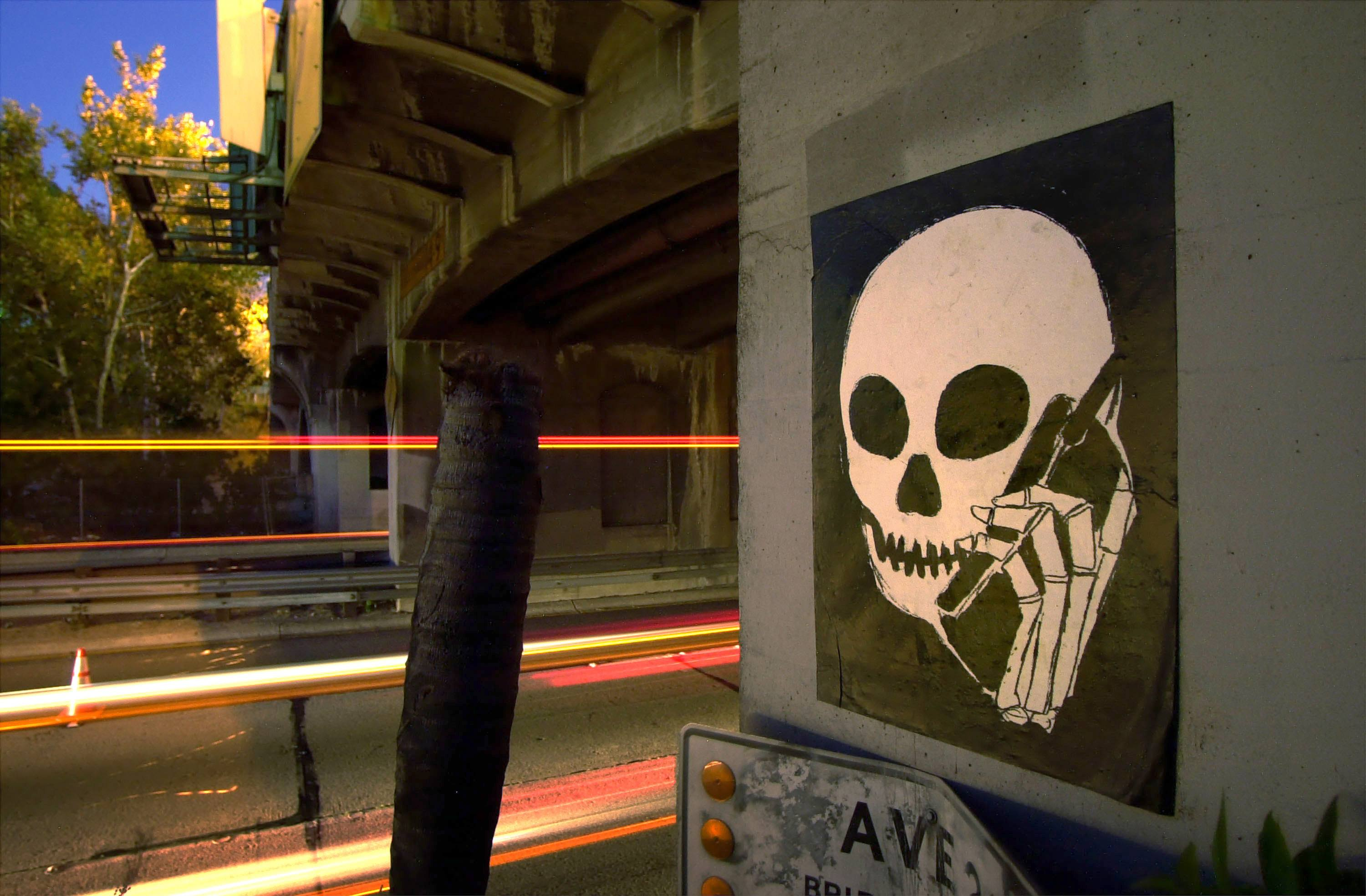 A graffiti image of a skull holding a cell phone is painted on an underpass along the Pasadena Freeway