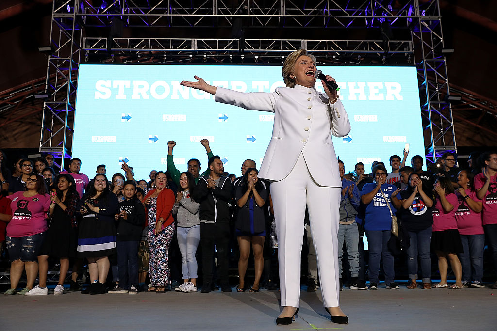 hillary clinton in a white pantsuit at a rally