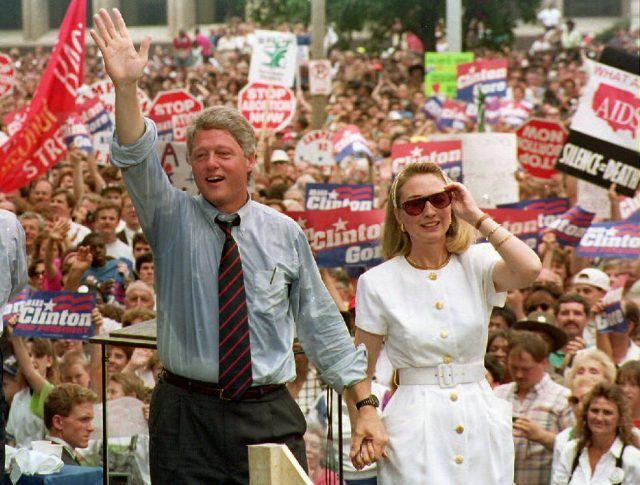 Bill Clinton waves at a crowd while standing next to Hilary Clinton.