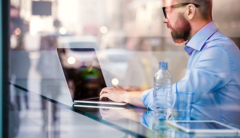manager sitting in cafe working on laptop