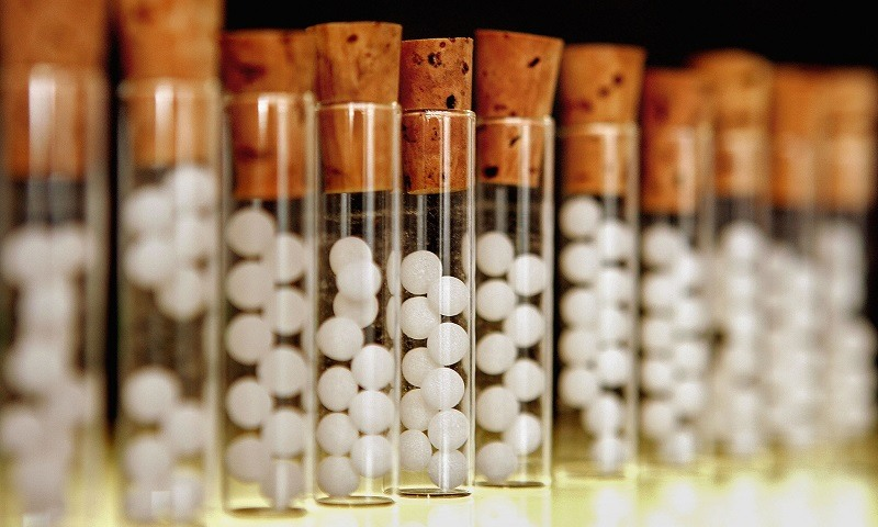 Vials containing pills for homeopathic remedies are displayed at a pharmacy