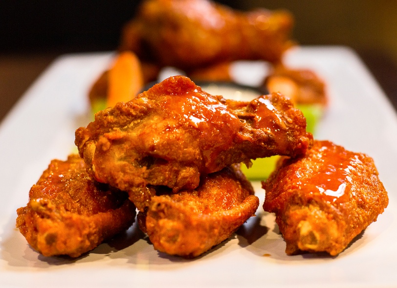 delicious hot wings dripping in sauce