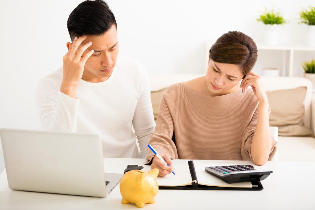 A husband and wife working on finances with calculator and laptop