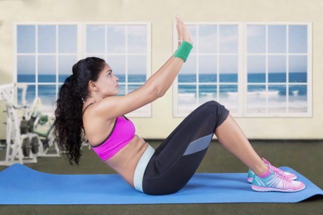 A woman does an ab workout on a blue mat.