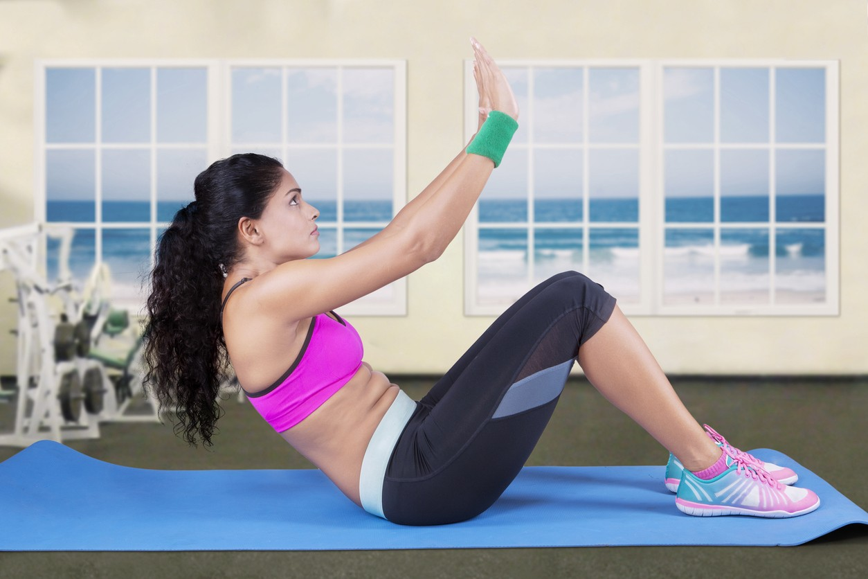 A woman does situps on an exercise mat
