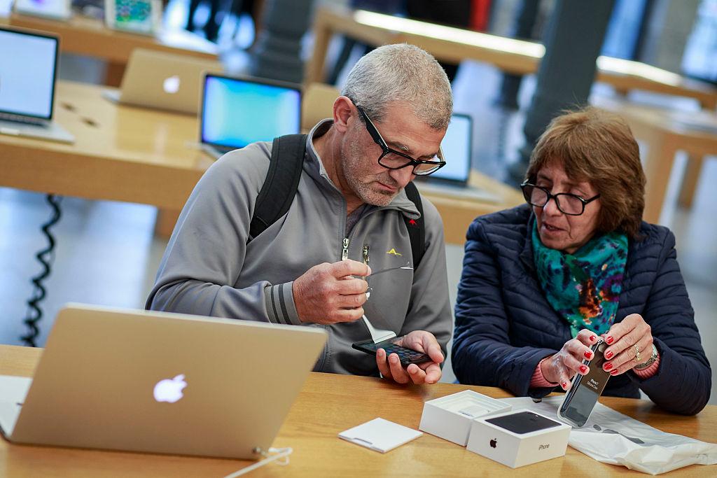 Customers handle a new Iphone 7 at Puerta del Sol Apple Store