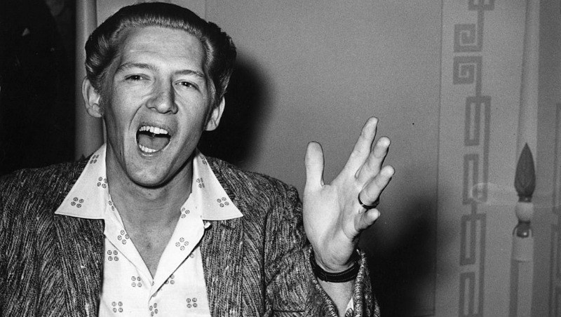 Jerry Lee Lewis talking and using his hands in a black and white photo