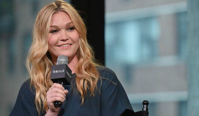 Julia Stiles sitting on a chair holding a microphone.