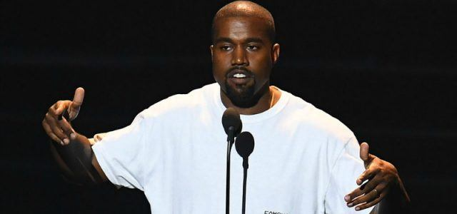 Kanye West in white t-shirt speaking into a microphone.