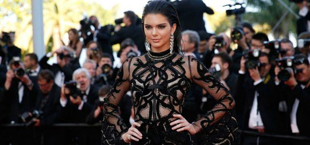 Kendall Jenner posing in a black lace dress with both hands on her hips.