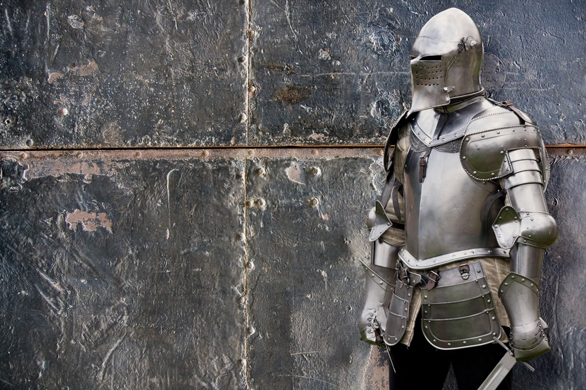 Knight in silver armored suit against the wall