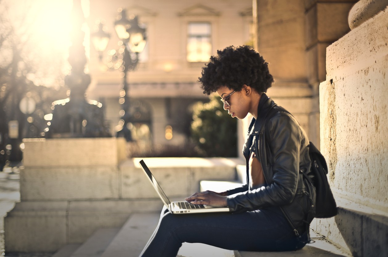 Woman working on laptop outside the building