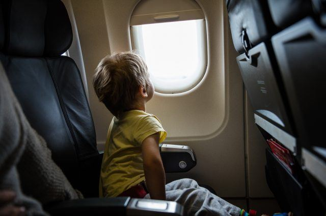 Little boy looking out of window in an airplane