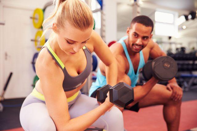 A man and woman exercise with dumbbells in a gym