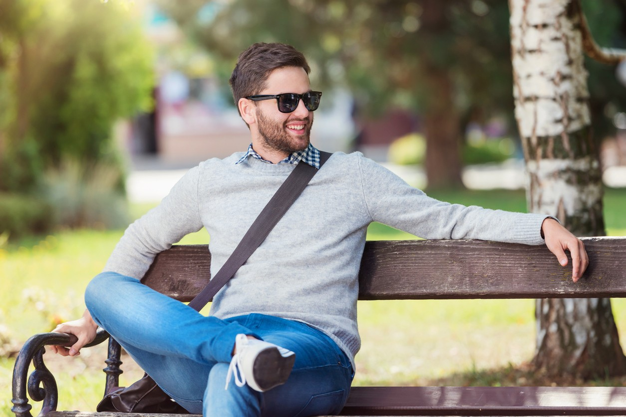 young man sitting on park bench