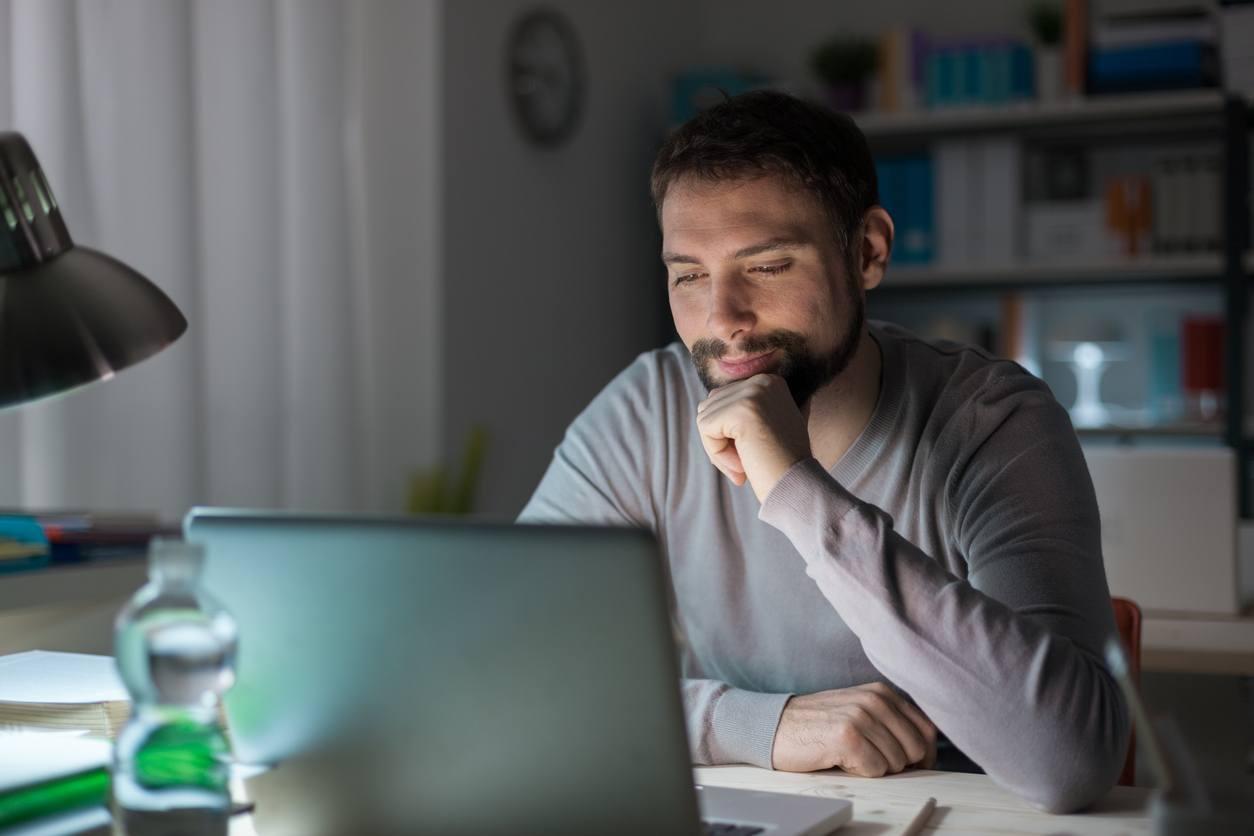 smiling man using a laptop at night