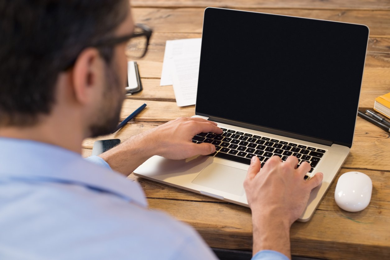 businessman sitting in front of laptop screen