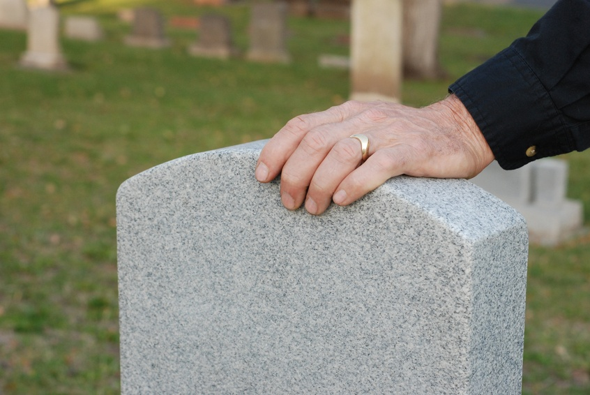 man's hand, with wedding ring, resting on a headstone