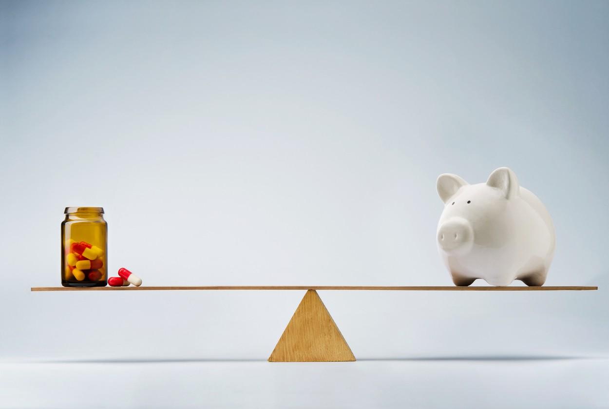 Piggy bank balancing on seesaw against medicine