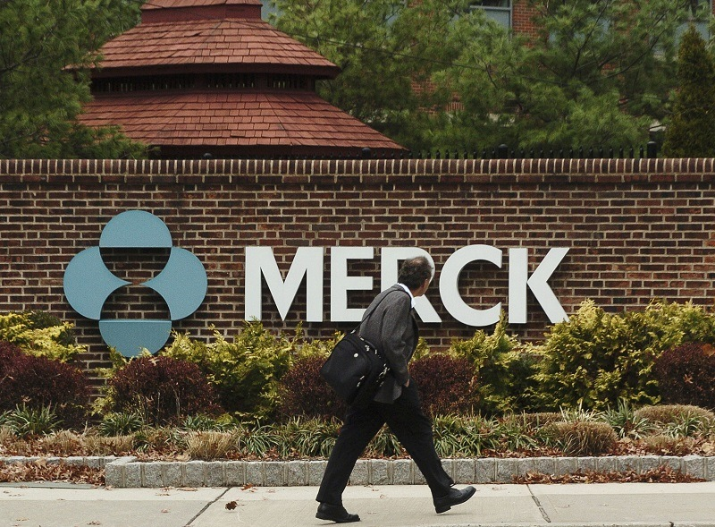 A man walks past a Merck sign
