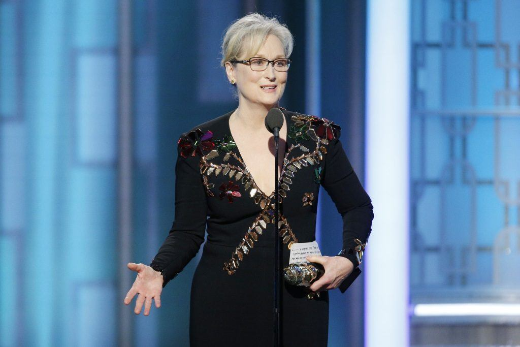 Meryl Streep holding an award and speaking into a microphone