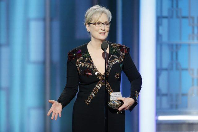 Meryl Streep holding an award and speaking into a microphone.