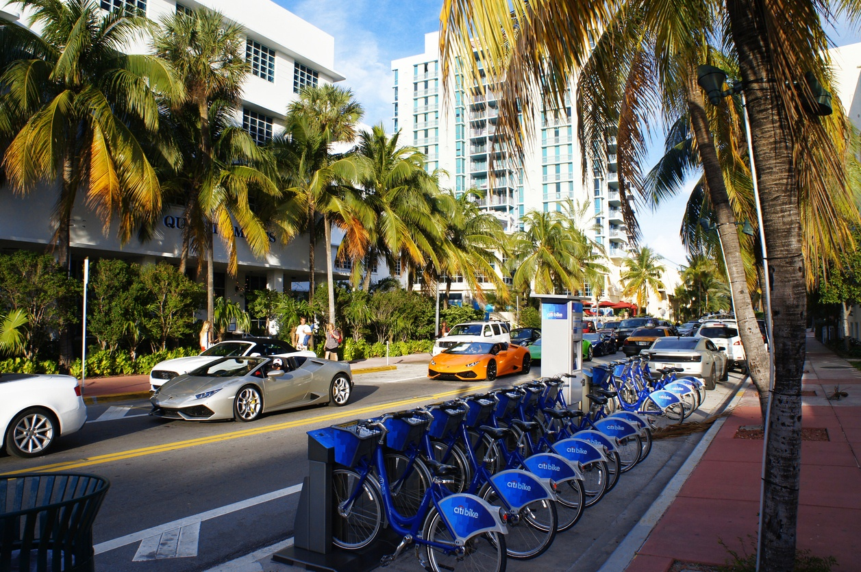 People and cars move down the street near bicycle parking